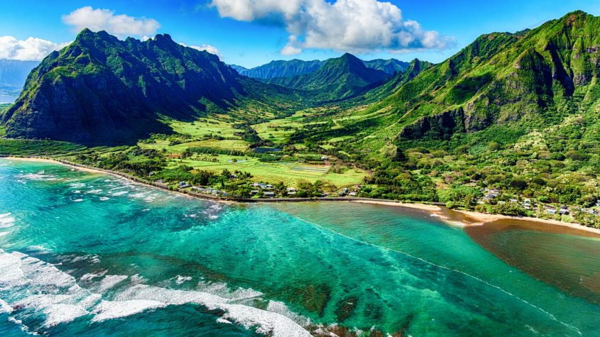 The beautiful and unique landscape of coastal Oahu, Hawaii and the Kualoa Ranch where Jurassic Park was filmed as shot from an altitude of about 1000 feet over the Pacific Ocean.